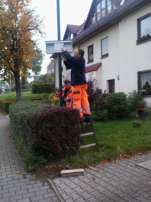 Frank Lommatzsch und Peter Schön vom Bauhof montieren das SpeedDisplay in Grillenburg